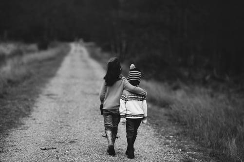 2 children walking down the road
