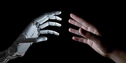 hands of human & robot touching